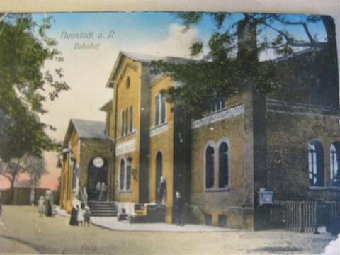Die colorierte Postkarte von 1907 zeigt den repräsentativen Bahnhof und Vorplatz