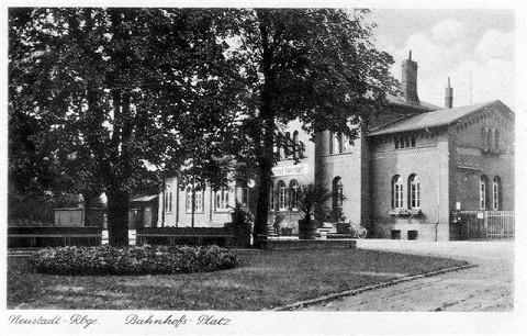 Die Postkarte des historischen Bahnhofsgebäudes und des Vorplatzes zeigt Bäume und Begrünung.