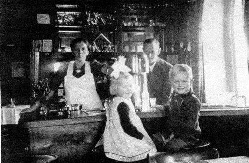 Innenansicht der Schankstube 1942: Frieda geb. Zinne und Herbert Scheve mit den beiden ältesten Kindern vor dem alten Tresen im Gasthaus Zur Eisenbahn um 1942 (Foto:Scheve privat)