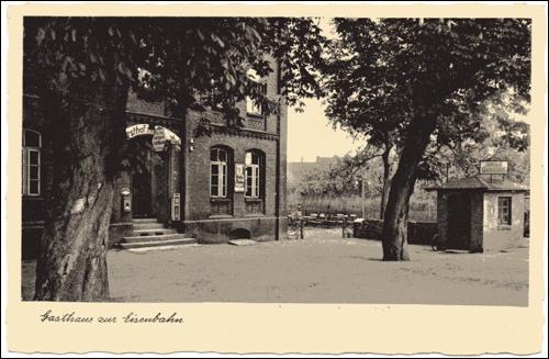 """Postkarte um1931:Gasthaus Scheve,Rechts das Wiegehäuschen der Fuhrwerkswaage. Auf dem Dach das Schild mit der Aufschrift """"Scheves Gartenlokal"""".In der Mitte der Kaffeegarten"""