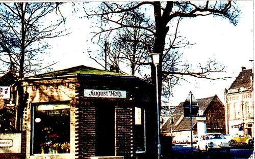 """Das einzig vorhandene Bild mit der """"Eierscheune"""" aus den 50er oder 60er Jahren. Es zeigt die Verkehrssituation an der Marktstraße zur Einfahrt zum Bahnhof. Links der Kiosk der Gärtnerei Holz an der Eisenbahn, rechts Gasthaus Scheve, mittig die """"Eierscheune"""". (Foto: Holz)"""